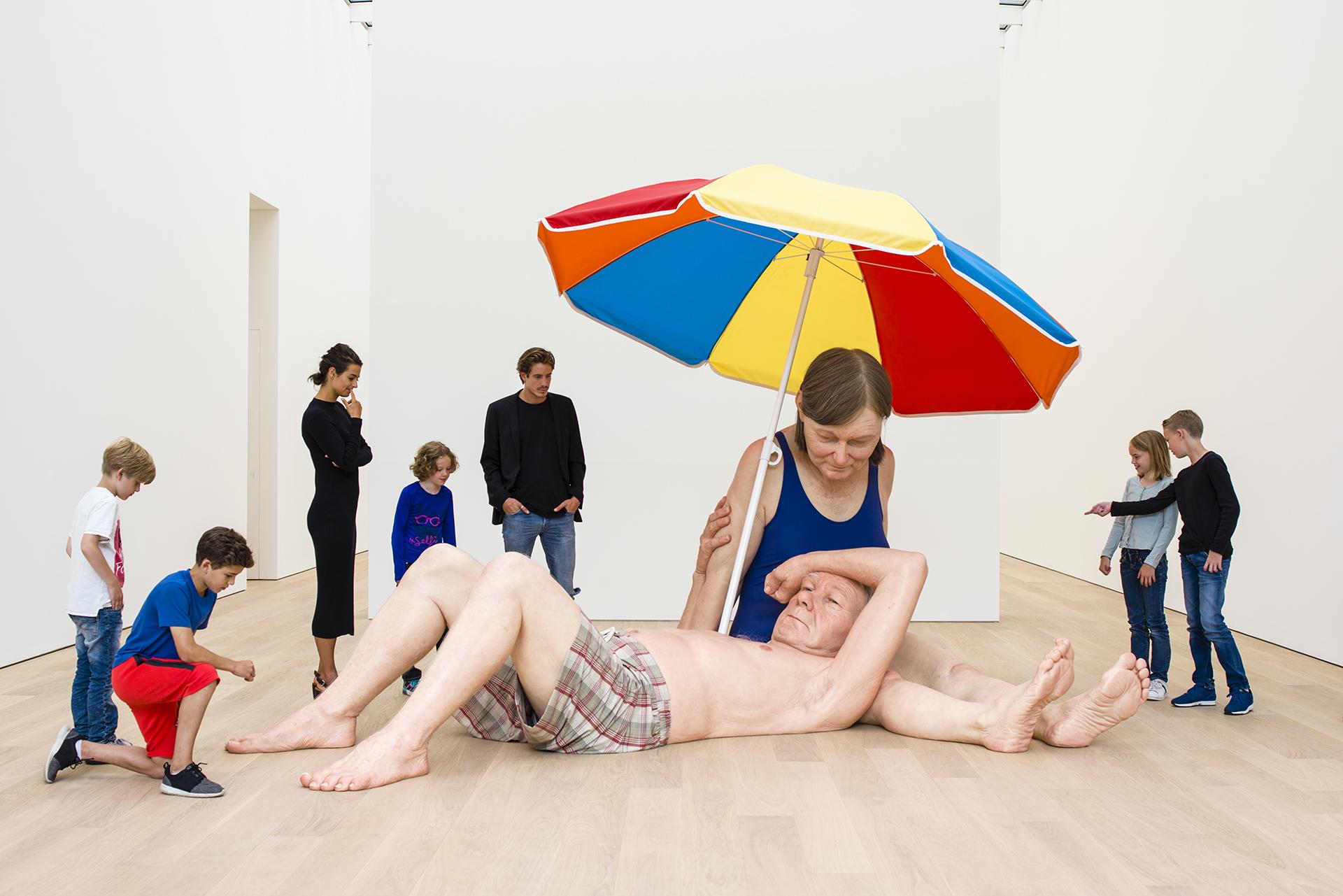 Kinderen kijken naar het kunstwerk Couple under an Umbrella van Ron Mueck