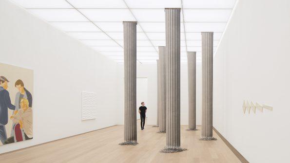 Man loopt door zaal met daarin palen die lijken op klassieke zuilen, maar die in werkelijkheid uit papier bestaat. Kunstwerk heet Colum Shred van de kunstenaar Christian Andersson